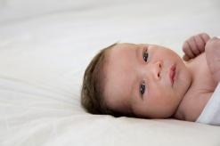 Awake baby, lying on white bedding making great eye contact.