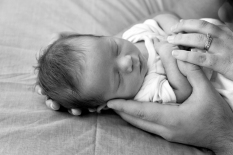Black and white image of a newborn, sleeping, mum and dads hands surrounding him.
