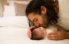 Father kissing newborn baby on cheek.