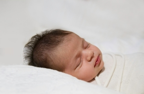 Sleeping newborn wrapped and photographed on white.