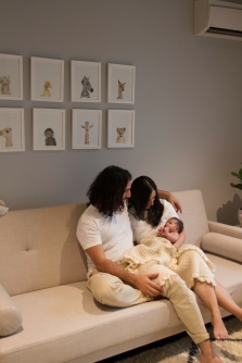 Lifestyle newborn session. Parents with newborn in the nursery.