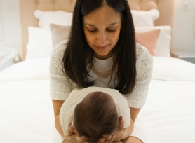 Close up of mother holding new baby. baby lying in mothers hands. Lifestyle newborn session,
