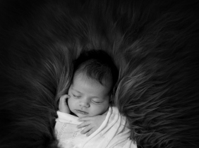 black and white newborn baby photograph. Baby asleep, wrapped lying on flokati fur.