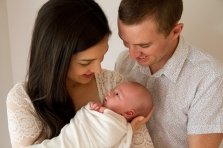 Parents posing with newborn baby during studio photography session,