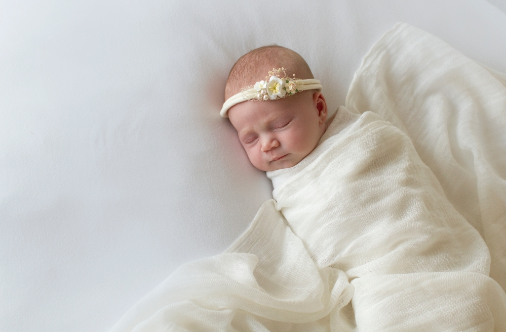 photograph of newborn baby during studio session. White on white with a small floral headband/tieback.