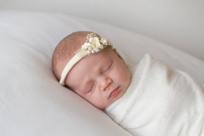 baby photographed on white with small white tieback