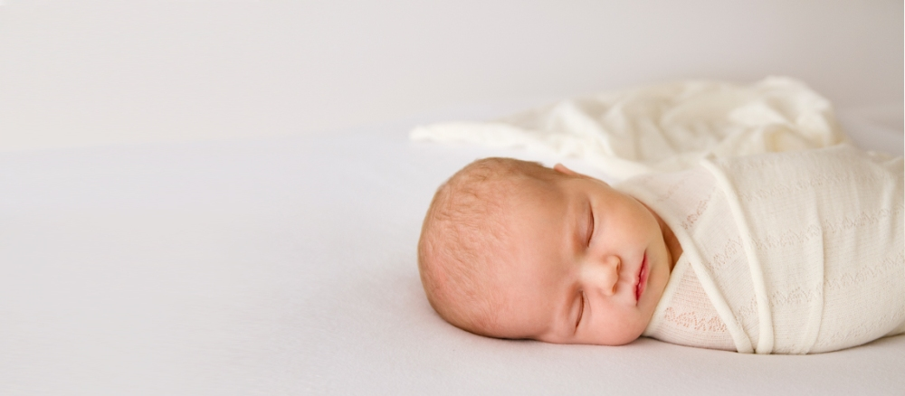 sleeping newborn wrapped in cream and white fabric. Wrap flowing behind baby. Studio photo shoot.
