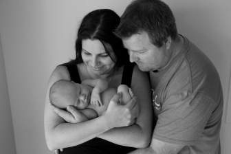 Mum and dad with newborn baby. Parents posing with newborn.